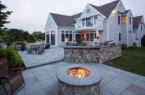 Gas fire pit with outdoor kitchen beyond